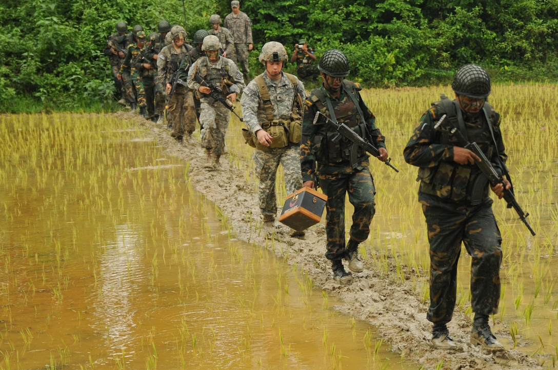 Soldiers march through rice paddy.