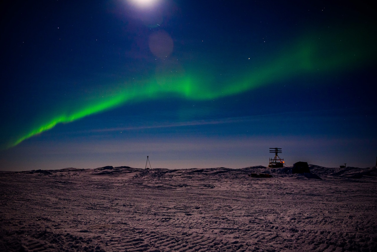Aurora borealis shines over camp on Arctic ice.