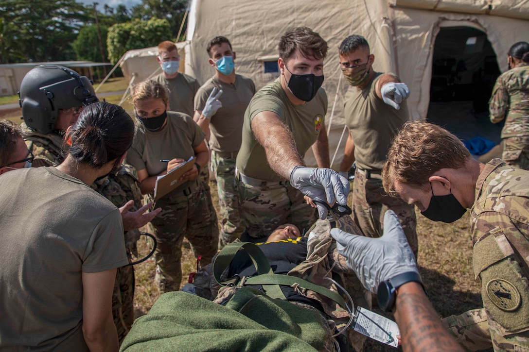 A group of soldiers work on a patient on a stretcher.