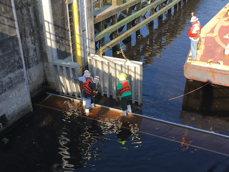 """On the lower end of the lock, crews must work across the girder in wetter conditions, wearing life vests for safety. The rigger or signalman on the barge keeps a close eye on the installation. He uses both a headset and hand signals to indicate """"stop"""" to the crane operator as the second needle is properly fitted in the slot. It takes a significant amount of experience and expertise for a crane operator to maneuver and place each needle down into the small slot, fitting them close enough together that the two pieces can be sealed together with a narrow black seal, visible on the left side of the second needle."""