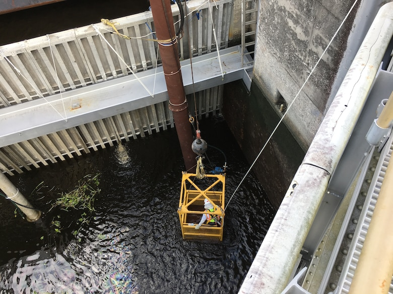 Once the water level has gone down, a 4 Man Basket is used to lower the crew into the chamber so they can remove vegetation and lift native fish up and out of the chamber.