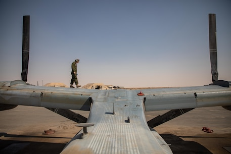 A U.S. Navy crew chief with Marine Medium Tiltrotor Squadron 166 (Reinforced,) assigned to the Special Purpose Marine Air-Ground Task Force - Crisis Response - Central Command 20.2, conducts a routine inspection for a MV-22B Osprey