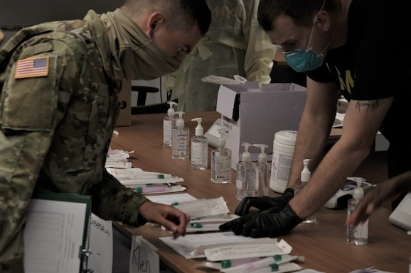 Medical Soldiers from the 7th Army Training Command, United States Army Garrison Bavaria, provide COVID 19 screening to U.S. Army Reserve Soldiers of the 7th Mission Support Command during in-processing for exercise Forward and Ready 20 at USAG Bavaria in Grafenwoehr, July 25, 2020.