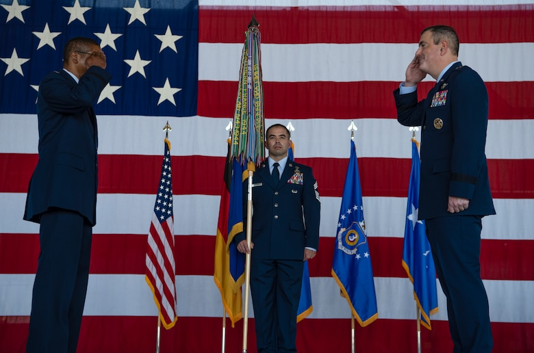 Two people saluting each other, while a third person is holding a guidon.