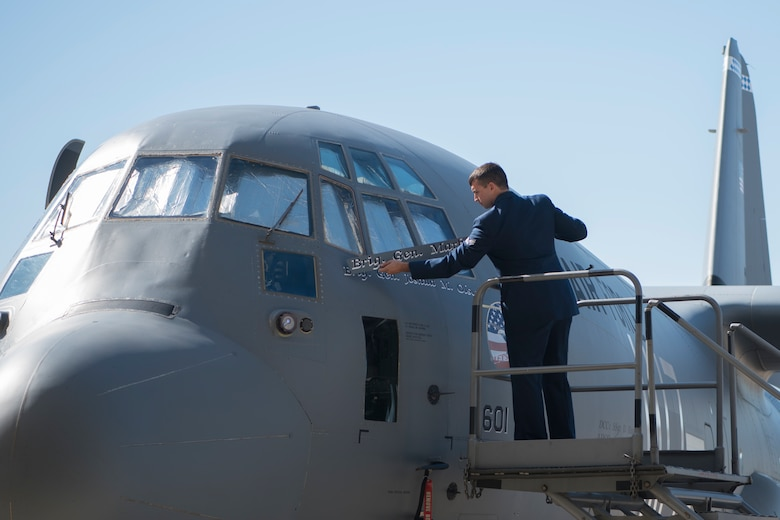 A man removing a name plate from an aircraft.