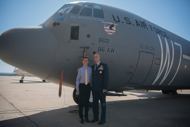 Two people standing in front of an aircraft.