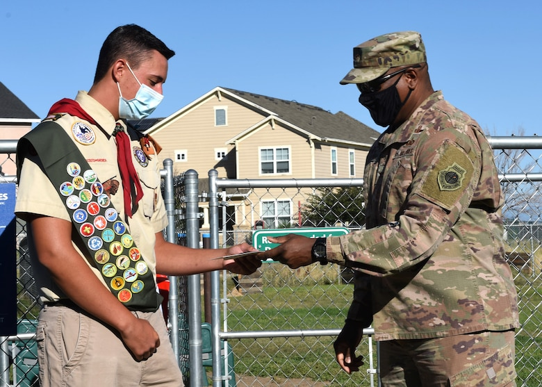 Col. Devin Pepper, Buckley Garrison commander, presents a memento to Spencer Fogg, Eagle Scout, for transforming the dog park on Buckley Air Force Base, Colo., Aug. 7, 2020. Fogg coordinated and completed the transformation of the dog park by installing ramps, hurdles, tunnels and poles to weave through at the dog park to fulfill his community service project requirement to become an Eagle Scout. (U.S. Air Force photo by Airman 1st Class Haley N. Blevins)