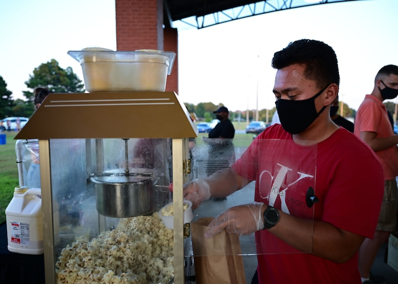 A man grabs popcorn from a machine