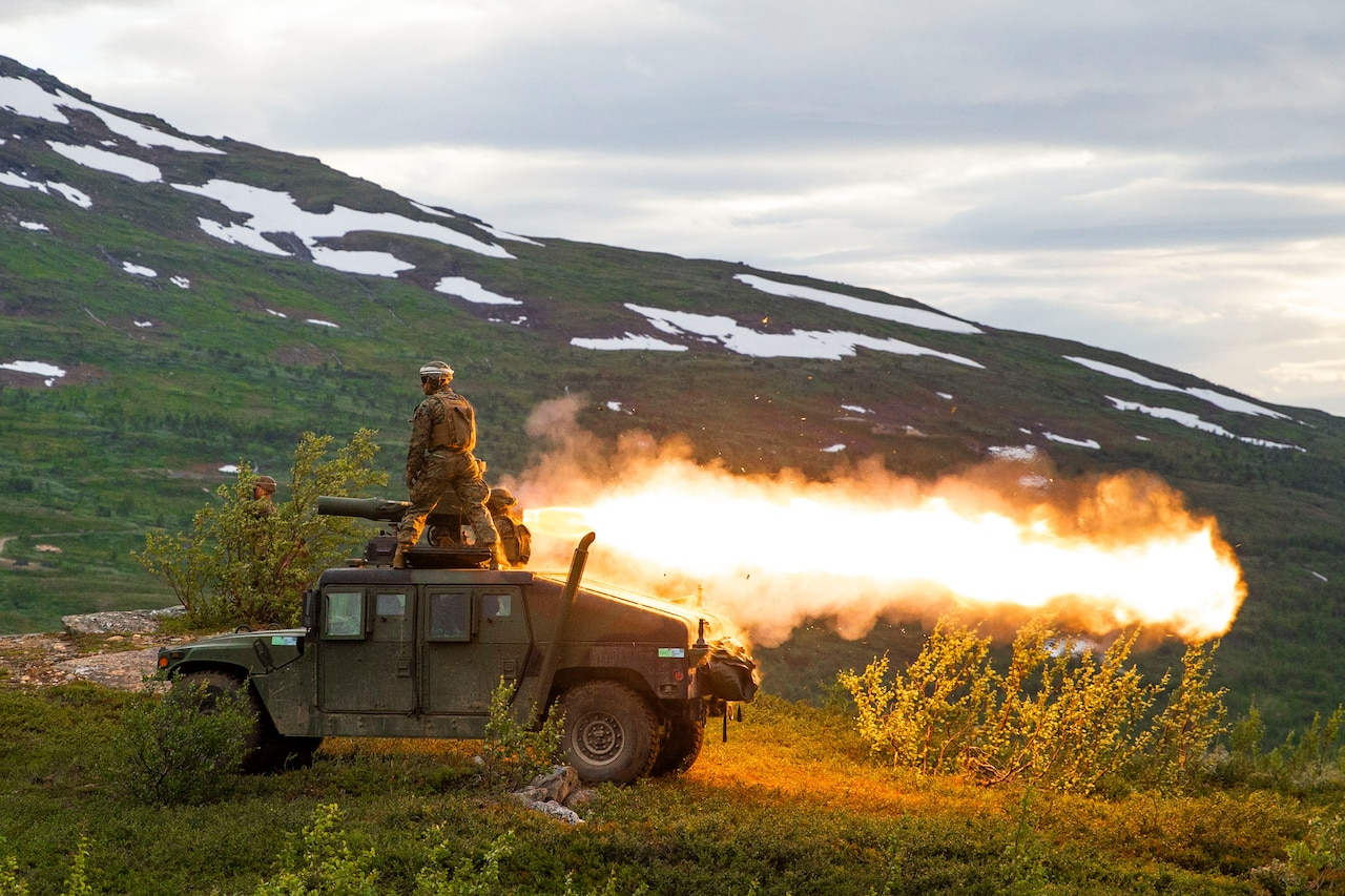 A Marine stands on a tank as a missile is fired near mountains.