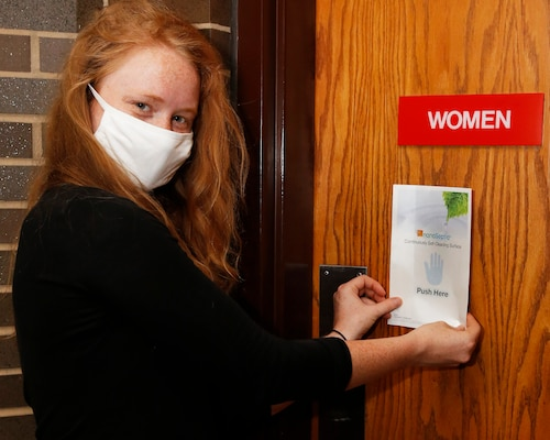 Nuclear Engineer (Code 2310.4) Cynthia Raines applies a NanoSeptic Protective Sheet to the high-touch area of a women's bathroom door in Bldg. 1500 at Norfolk Naval Shipyard.