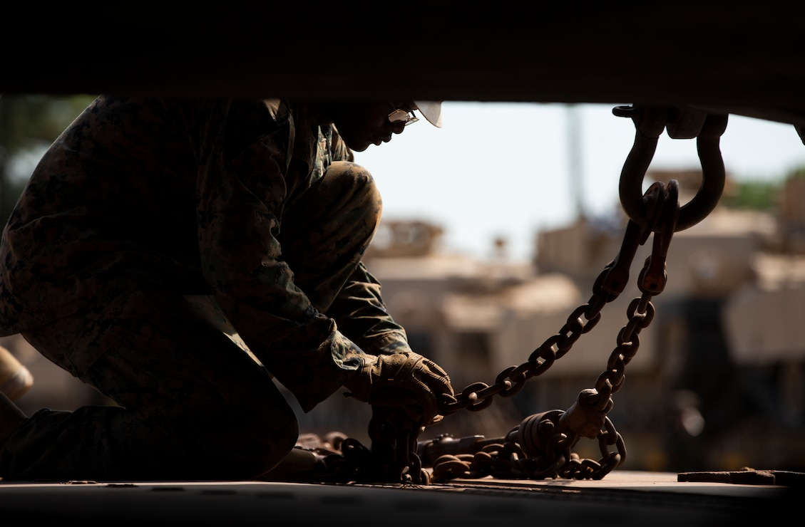 A U.S. Marine tightens a chain securing an M1A1 Abrams tank during the drawdown of Marine Corps armor divisions at Camp Lejeune, North Carolina, July 28.