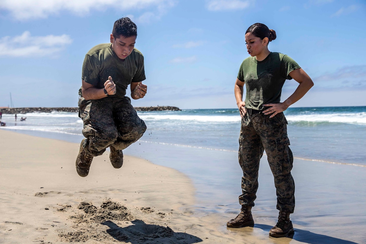 A Marine jumps next to another Marine on a beach.