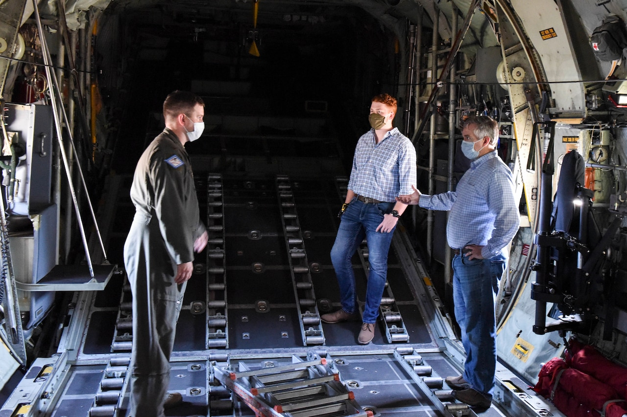 An officer wearing a flight suit talks with two civilians in the cargo bay of a transport aircraft. All are wearing face masks and practicing social distancing.