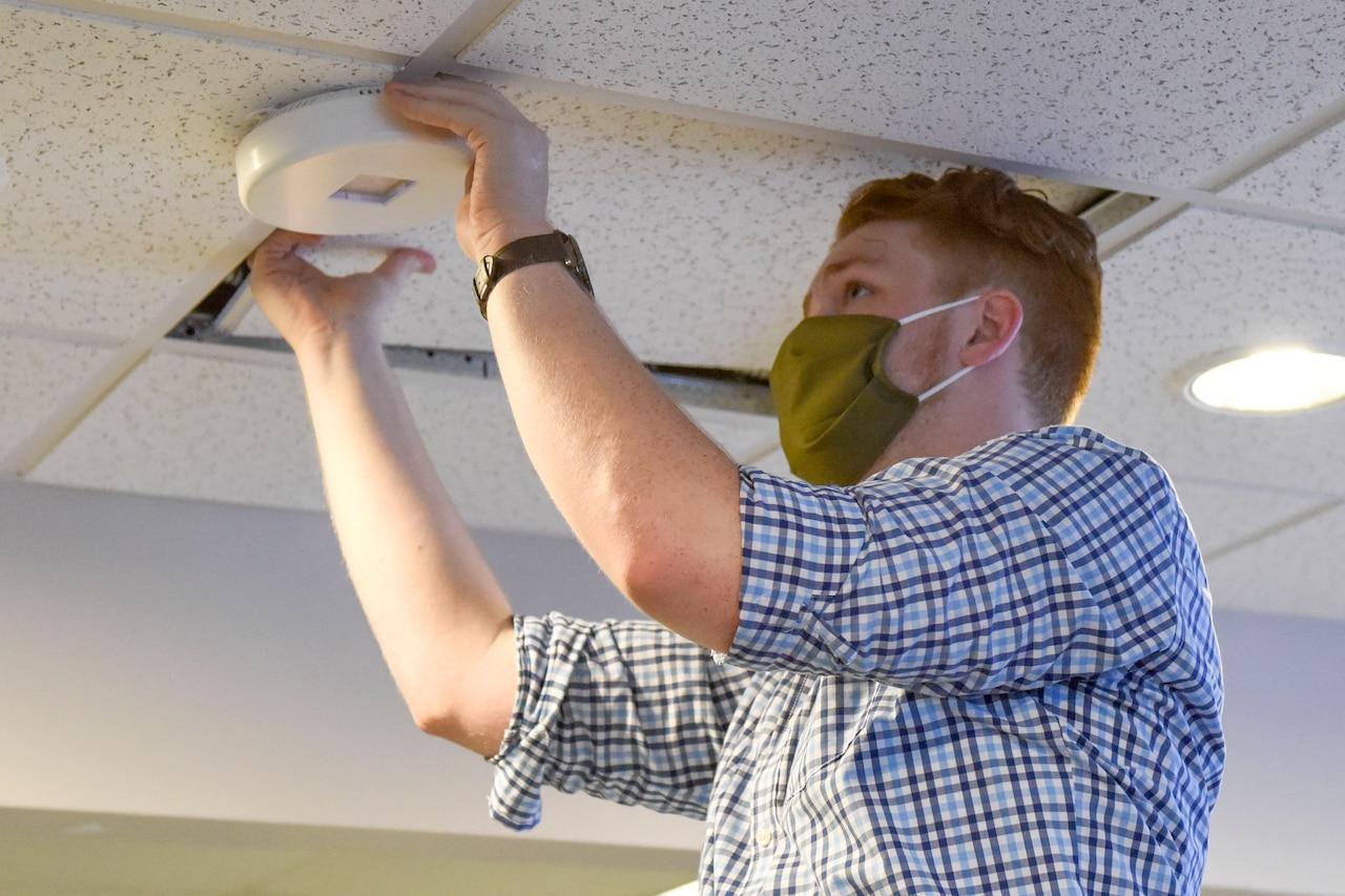 A man wearing a face mask installs an ultraviolet light on a ceiling.