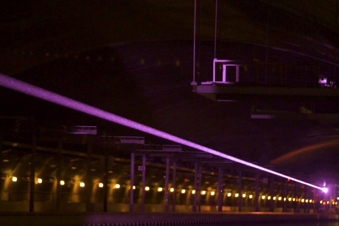 A laser shoots across dark surroundings.