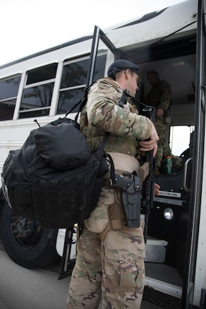 A Utah Air National Guard Airman boards a bus on their way to  downtown Salt Lake City, Utah