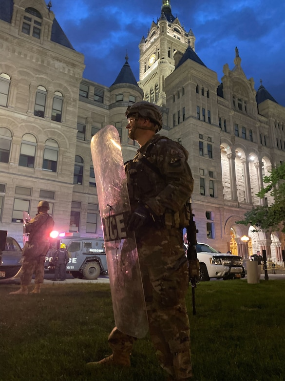 A Utah Air National Guard Airman stands with a riot shield to protect a building in downtown Salt Lake City, Utah