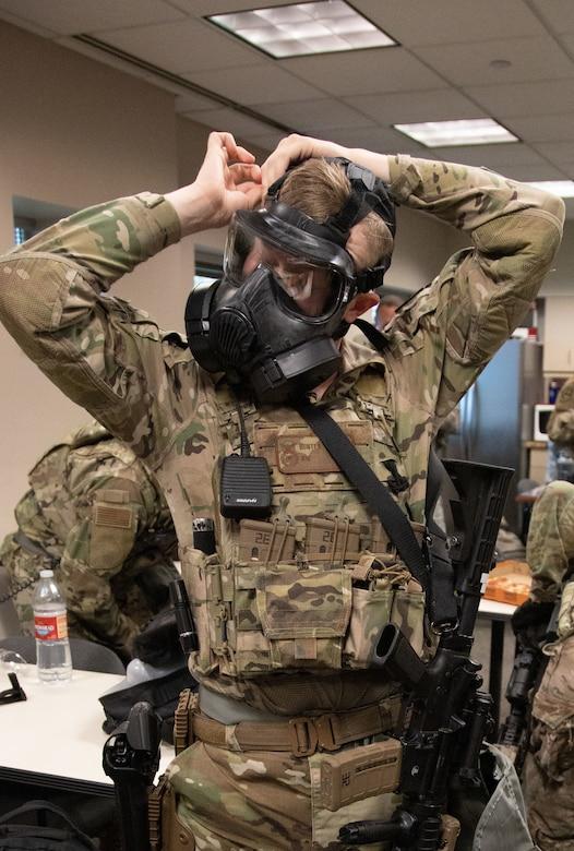 A Utah Air National Guard Airman fits a gas mask while preparing to head to downtown Salt Lake City, Utah