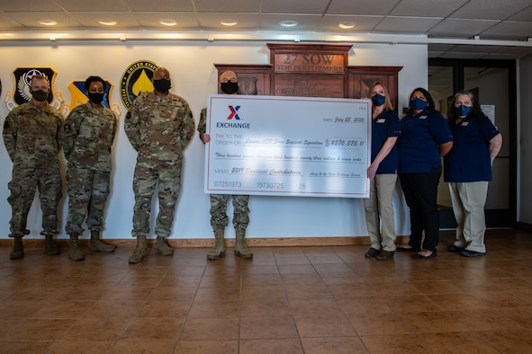 Cannon Air Force Base Army and Air Force Exchange Services management presents 27th Special Operations Wing leadership with a symbolic check representing their annual donation to the wing's Morale, Welfare and Readiness Fund at the base July 31st, 2020. The annual donation from AAFES helps fund 27th Special Operations Force Support Squadron quality of life services. (U.S. Air Force photo by Senior Airman Maxwell Daigle)