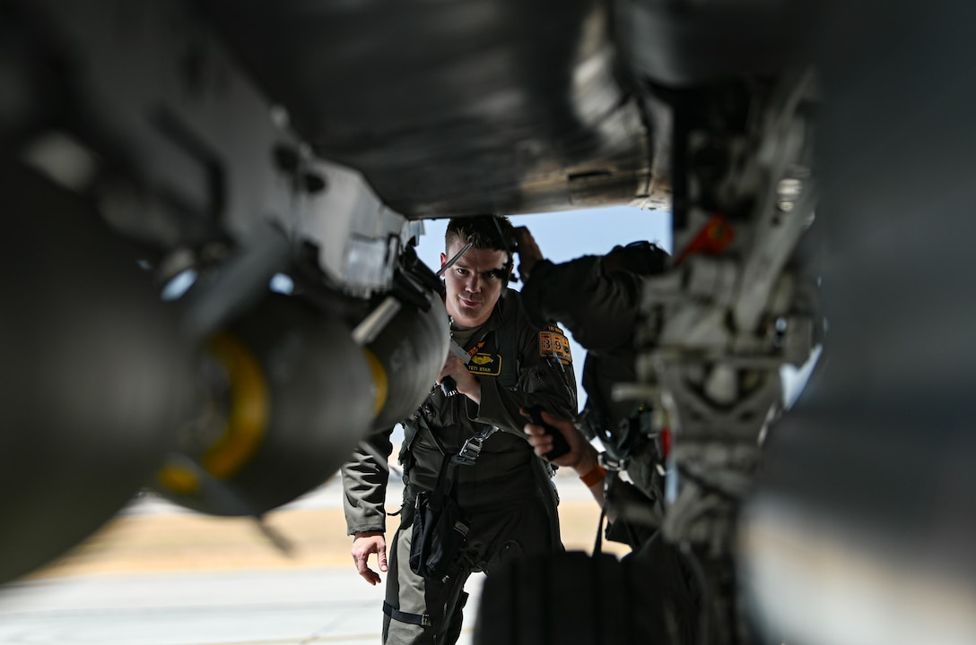 Pilot looks under jet.