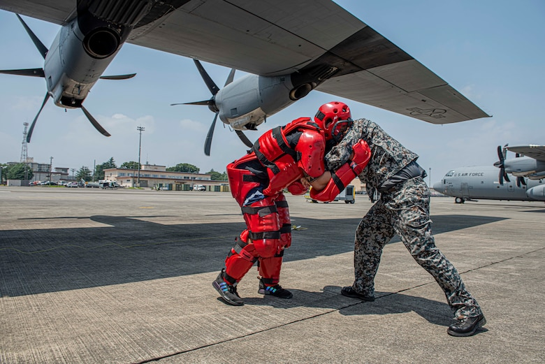 A Koku-Jieitai (Japan Air Self-Defense Force) member reacts to a simulated intruder by implementing a combative technique learned during a bilateral aircraft security training event at Yokota Air Base, Japan, August 7, 2020