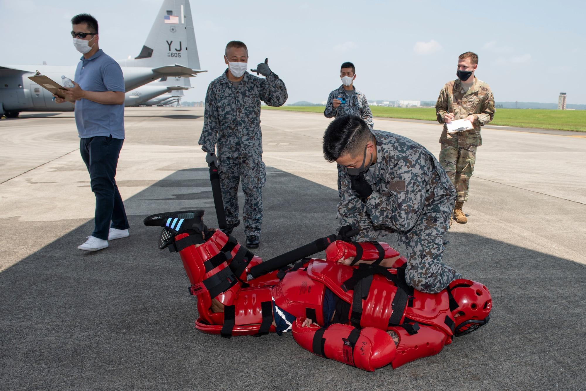 A Koku-Jieitai (Japan Air Self-Defense Force) member apprehends a simulated intruder during a flightline intrusion scenario as a portion of the bilateral aircraft security training at Yokota Air Base, Japan, August 7, 2020.