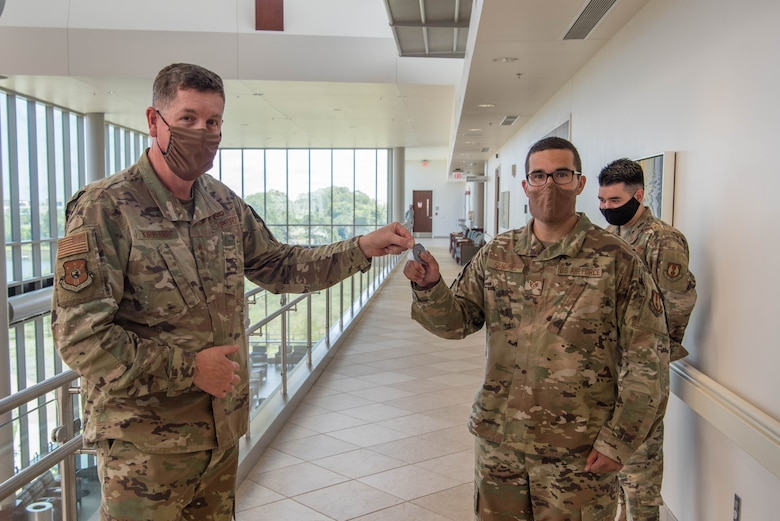 Two Airmen holding AFSC Commander's coin