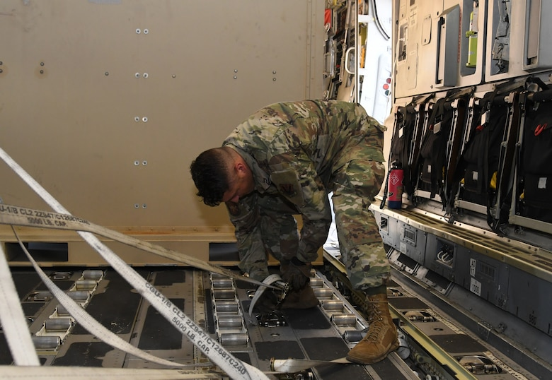An Airman unhooks cargo from the floor of a plane.