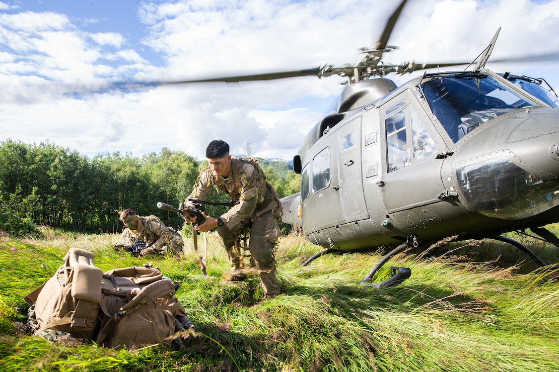 U.S. Marines prepare their weapons after exiting a Norwegian-operated Bell 412 helicopter during Midnight Sun, a battalion force-on-force field exercise in Setermoen, Norway, Aug. 5.