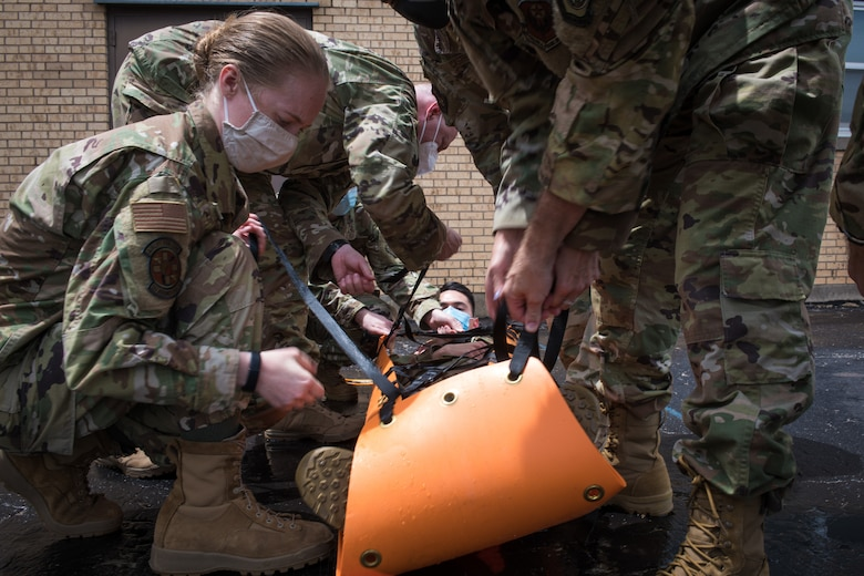 Airmen strap a simulated patient into a stretcher