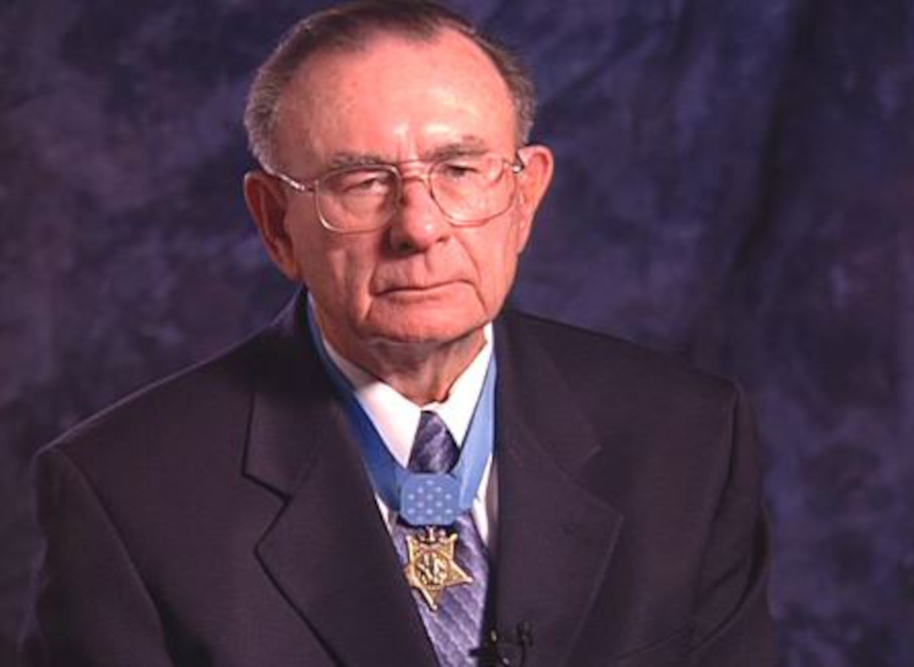 An older man in a suit wears a Medal of Honor.