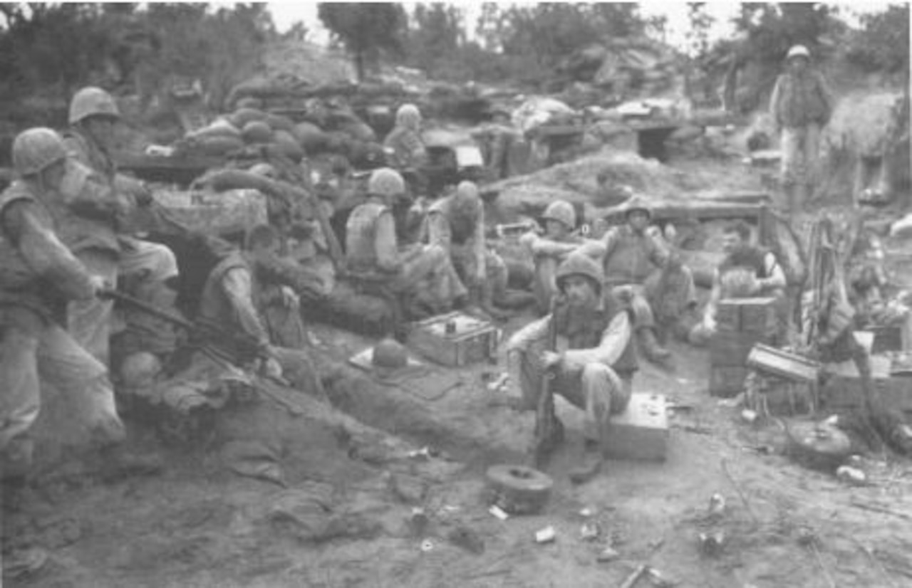 Several men in helmets sit around near a bunker.