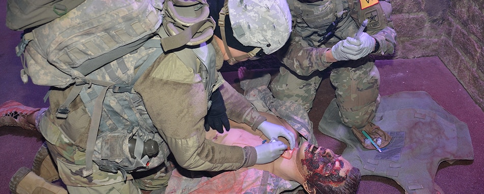 """Department of Combat Medic Specialist Training program students at the Medical Education and Training Campus on Joint Base San Antonio-Fort Sam Houston, Texas, conduct an emergency cricothyrotomy on a """"casualty"""" during simulation training."""