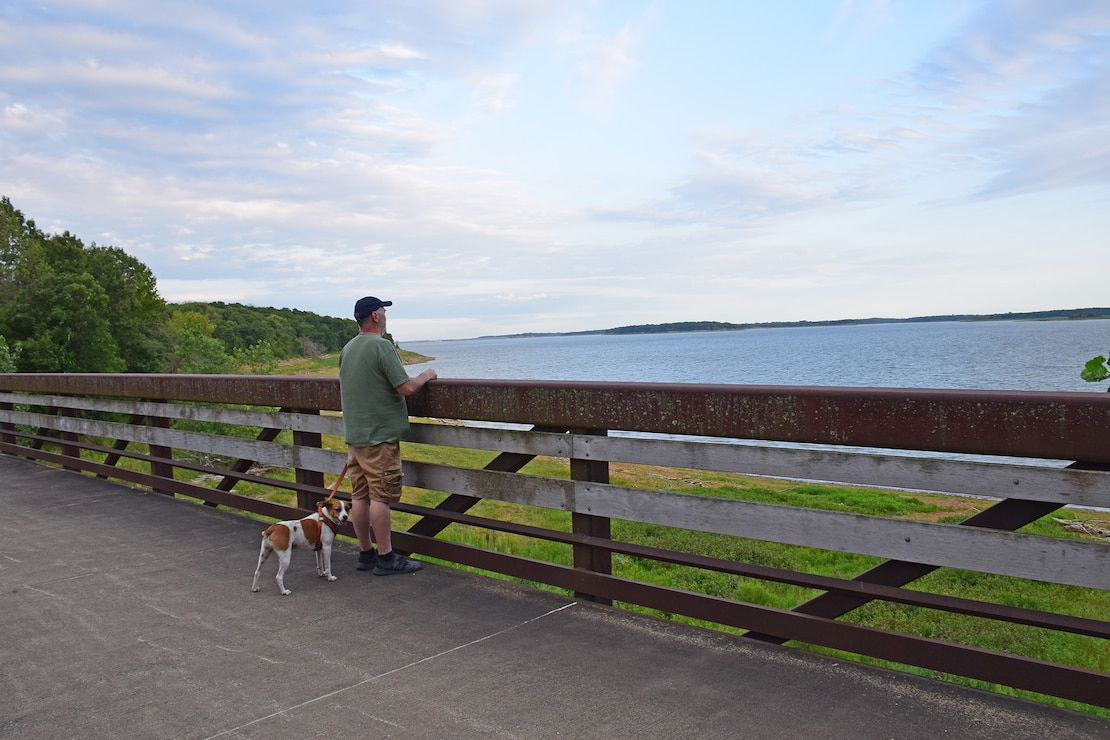 A man walking his dog on the Volksweg Trail stops to look out at Lake Red Rock near Pella, Iowa.