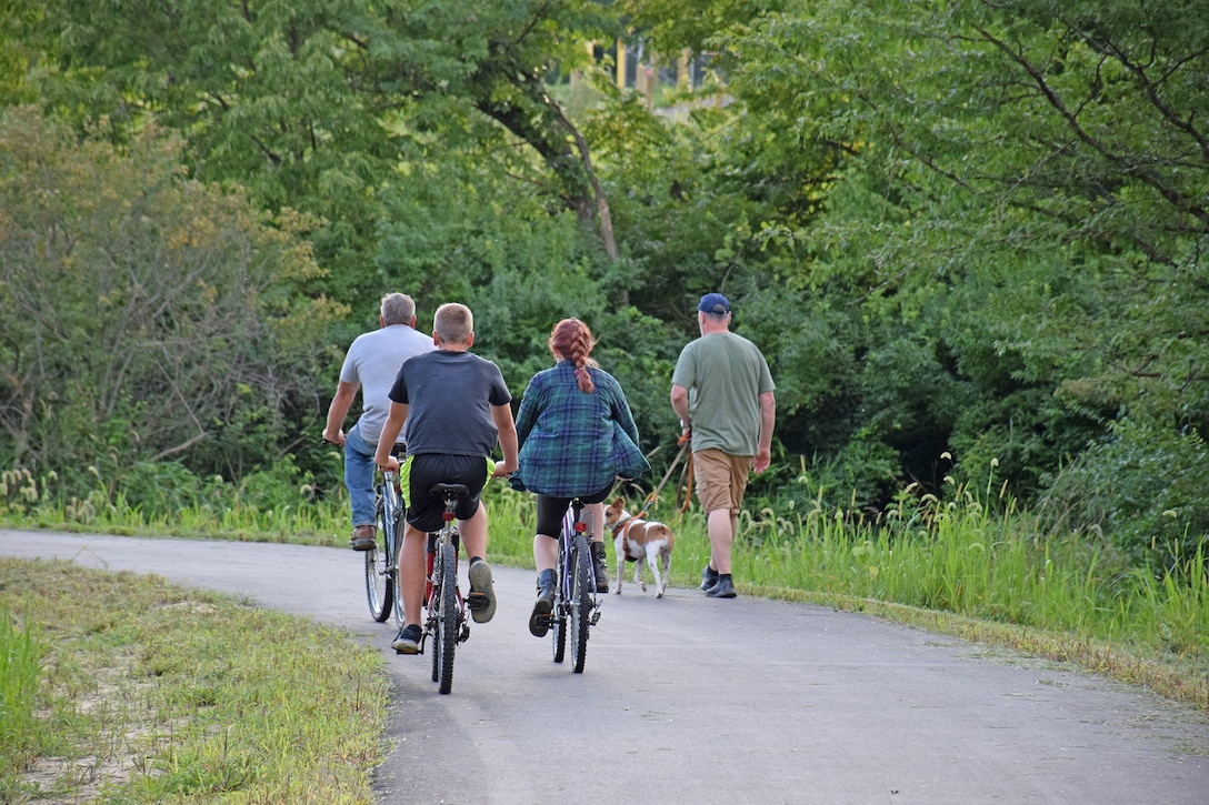 A group of bicyclists pass a man walking his dog on the Volksweg Trail near Lake Red Rock.