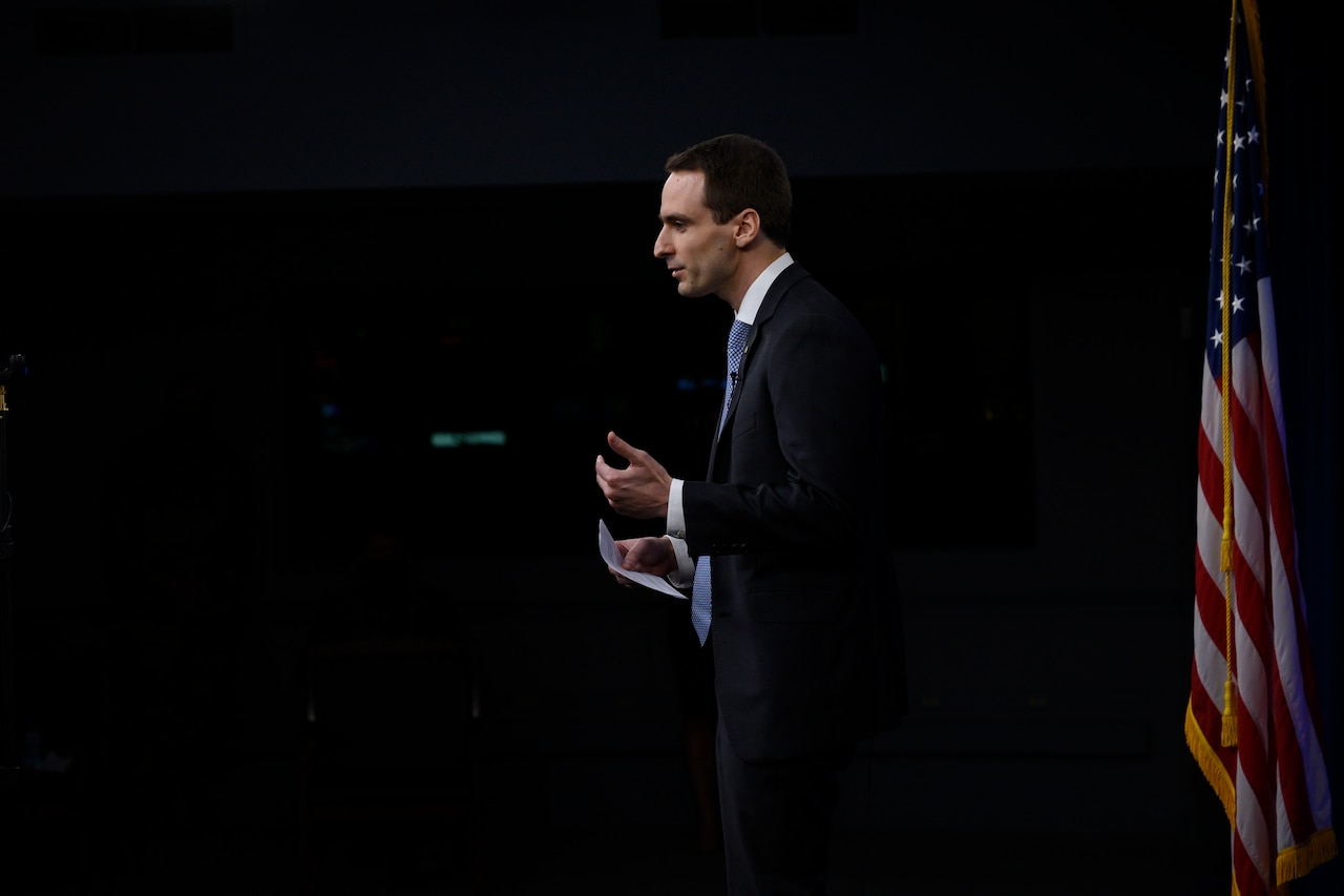 A man stands in a dark room facing an audience. A U.S. flag is behind him.