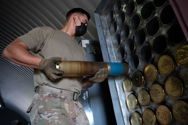 Senior Airman Cody Heathcock, a conventional maintenance specialist assigned to the 27th Special Operations Maintenance Squadron munitions flight, loads a 105 MM round into a temporary storage container at Cannon Air Force Base, N.M., July 22, 2020. 105 MM rounds are loaded into these containers until they are prepared for movement on trailers and stored until needed.  (U.S. Air Force photo by Senior Airman Maxwell Daigle)