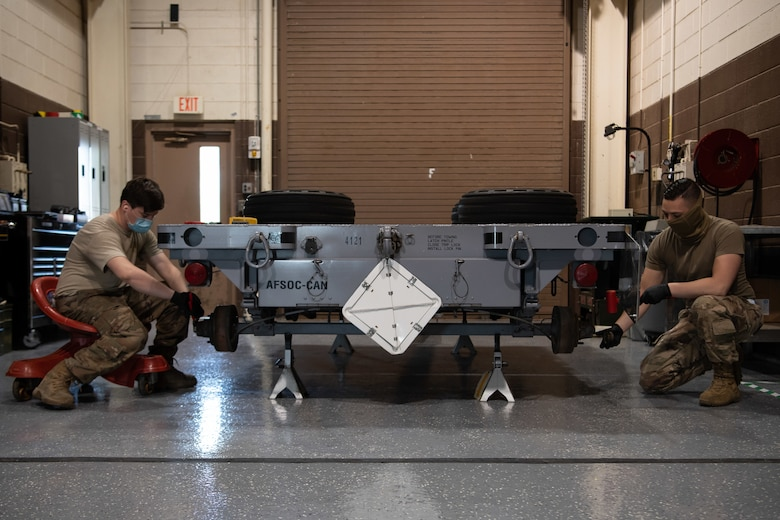 Senior Airman Tyler Currey, left, and Senior Airman Brandon Richey, trailer maintenance specialists assigned to the 27th Special Operations Maintenance Squadron munitions flight, perform a 720-day inspection on a MHU-141 trailer at Cannon Air Force Base, N.M. July 22, 2020. MHU-141 trailers are used to transport munitions and are carefully maintained and inspected to ensure safe transportation of their cargo.  (U.S. Air Force photo by Senior Airman Maxwell Daigle)