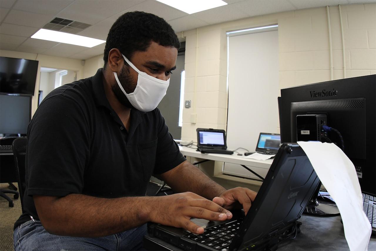 Man operates computer.