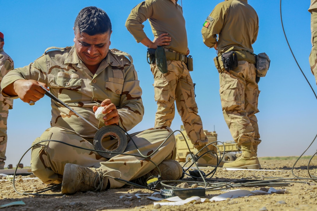 A man in a military uniform unrolls tape from a spool. Other military personnel stand nearby.