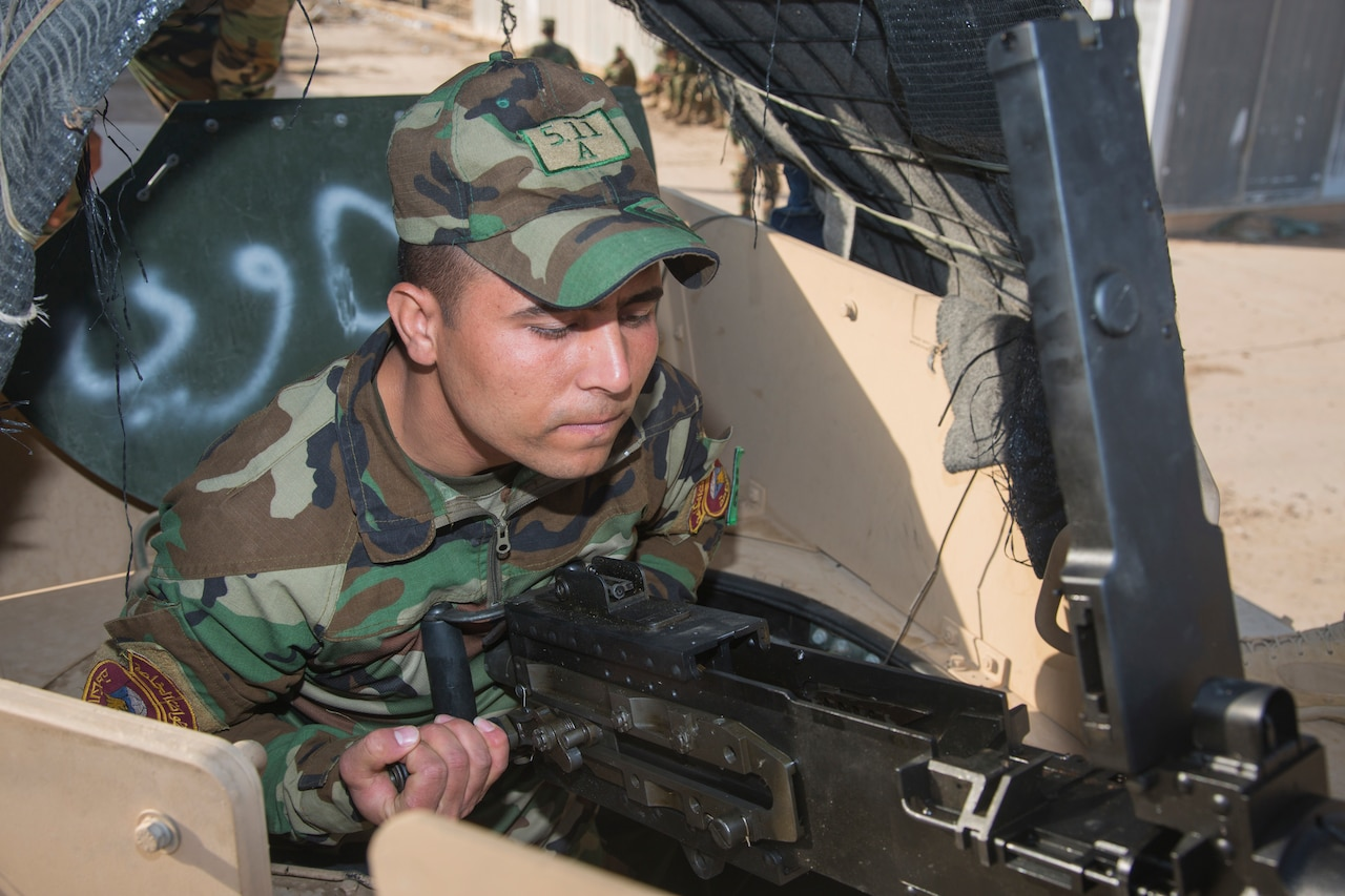 A man in a military uniform performs operations on a large gun.
