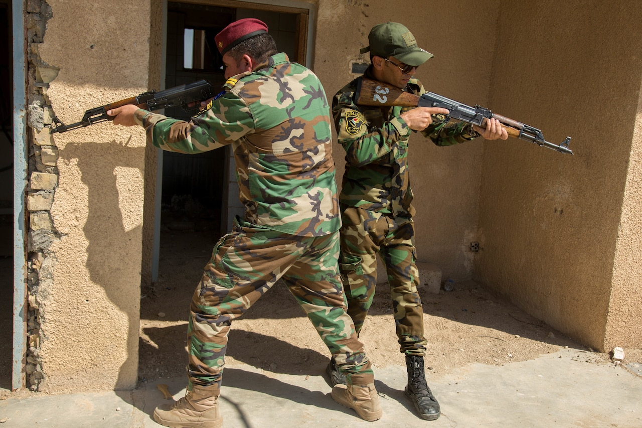 Two men in military uniforms face in the opposite direction and aim rifles.