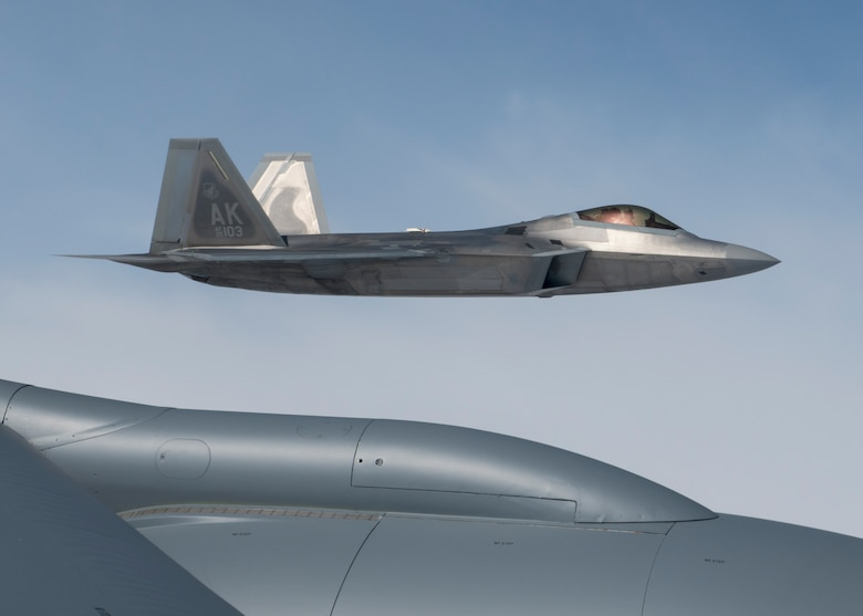 A U.S. Air Force F-22 Raptor from the 354th Fighter Wing flies in formation by a KC-135 Stratotanker from the 92nd Air Refueling Wing during field training exercise Red Flag Alaska 20-3, Aug. 4, 2020. RFA 20-3 is conducted over the Joint Pacific Alaska Range Complex with air operations flown primarily out of Eielson Air Force Base and Joint Base Elmendorf-Richardson, Alaska. (U.S. Air Force photo by Senior Airman Lawrence Sena)