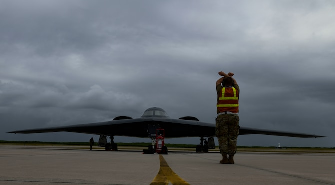 Staff Sgt. Mark Farrar, 131st Aircraft Maintenance Squadron crew chief stationed at Whiteman Air Force Base, Missouri, marshalls a B-2 Spirit Stealth Bomber as it arrives at Naval Support Facility Diego Garcia, Aug. 12, 2020. Three B-2 Spirits from Whiteman AFB deployed to NSF Diego Garcia to support U.S. security commitments in the Indo-Pacific region. (U.S. Air Force photo by Tech. Sgt. Heather Salazar)