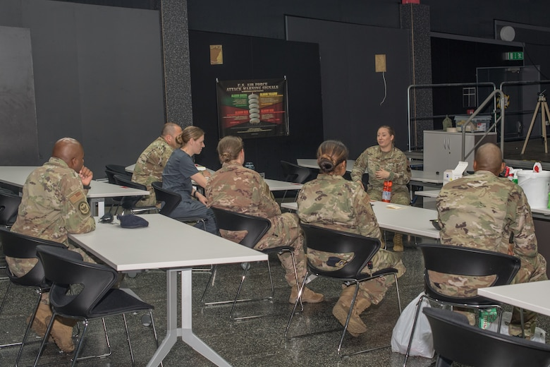 A group of military service members sitting at a meeting.