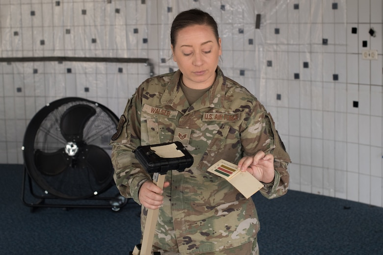 An Airman holding a stanchion and chemical detection paper.