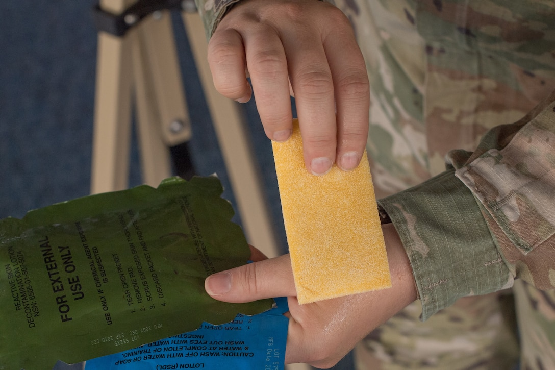 A close-up of the hands of an Airman holding a decontamination sponge.