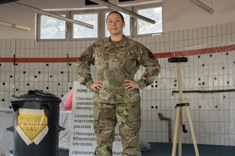 An Airman standing in front of emergency management training material.