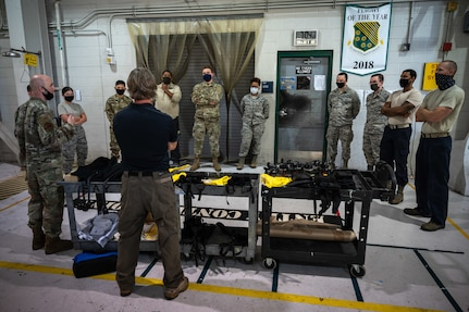 Airmen surround a table with equipment to learn how to use it.