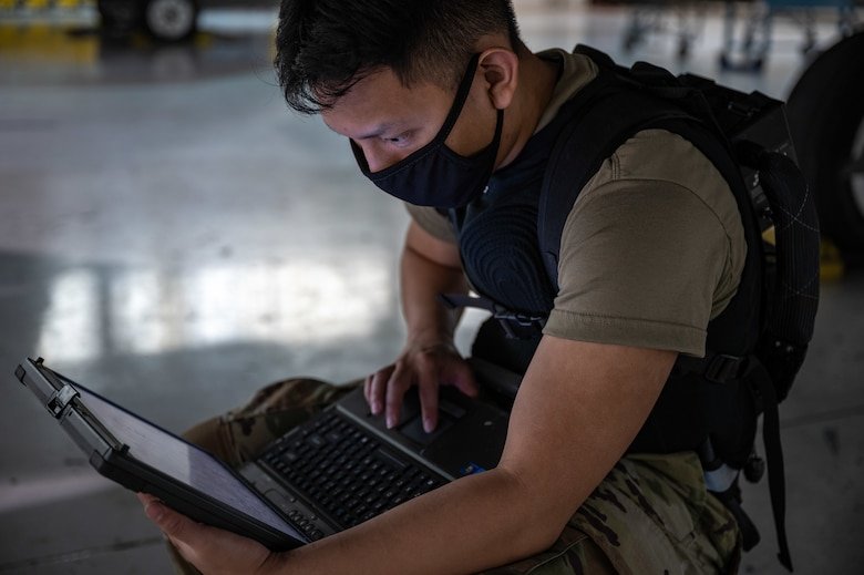 An Airman works on a laptop while under an F-22 Raptor.